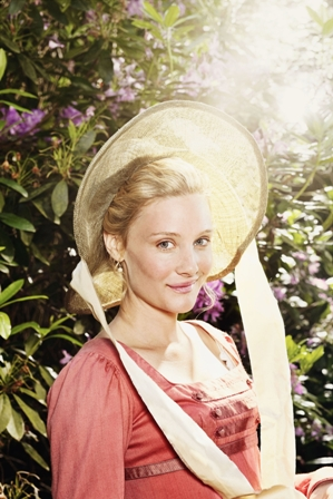 Emma (Romola Garai) wearing a bonnet and pink dress in front of a bush
