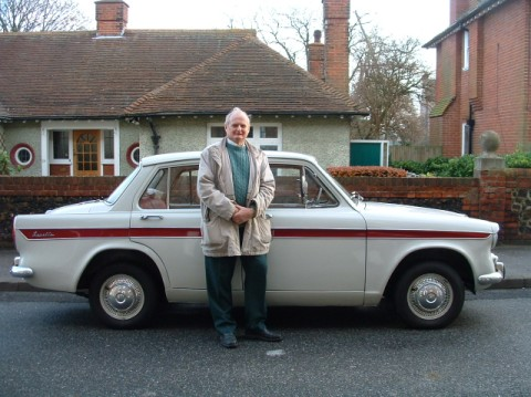 Paul Hicks standing by a car in front of a house