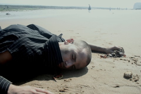 Man lying on the beach with torn clothes