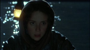 Lizzie Hexam (Keeley Hawes) in a hooded cape in a boat on the medway. A close up of her face with the water behind her and the boat lanten.