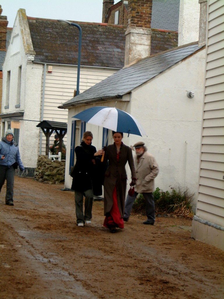Rachel Stirling dressed in a red victorian style dress is walking under an umbrella being held by a member of the production team. They are walking down a narrow street in Whitstable surrounded by small white houses.