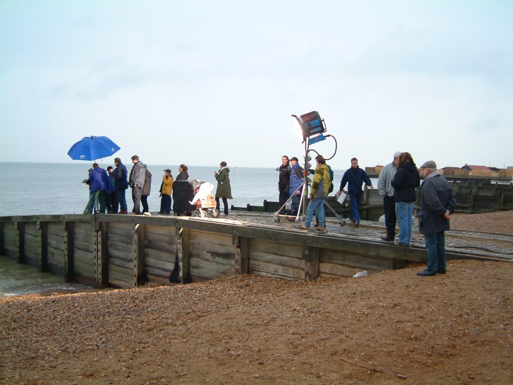 Photograph of a handful of the production team standing on the jetty on Whitstable beach.