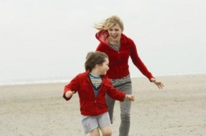 Michelle Williams chasing Sidney Johnson on a beach - wearing similar outfits red jumpers and neatral trousers
