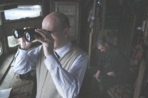 Alex MacQueen looking out of binoculars and Phillip Campbell in the Bird hide out