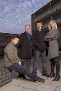 From left to right: Jody Lee Latham (sitting), Peter Mullan, Andrew Buchan and Tamsin Outhwaite are all placed infront of a tower block with a blue sky in the background