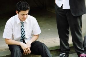 Lance (Jamie Mander) in a school uniform sitting on a pavement