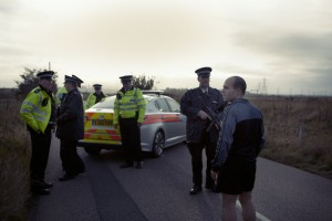 Paul Gould (Anatol Yusef) standing in a country road which the police have closed off