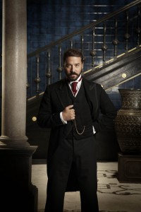 Jeremy Piven as Harry Selfridge - dressed in a suit, holding a pocket watch in front of a pillar and staircase