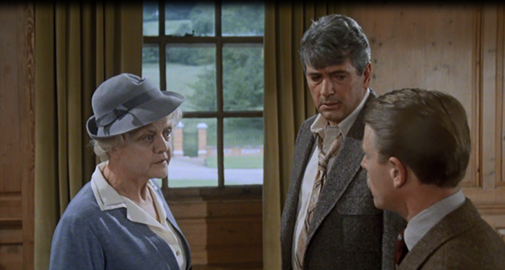 Angela Lansbury is talking with Rock Hudson and Edward Fox inside St Clare Estate. The room has wooden pannelling and they are all standing in front of a window where you can see the grounds through.