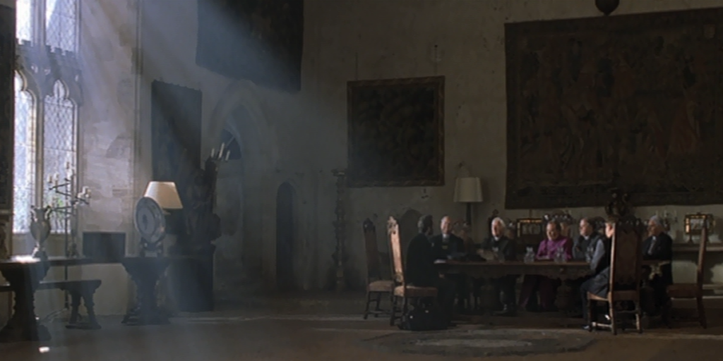 A still of Barons Hall at Penshurst Place. The room is decorated in medieval decor and the Bishop and a handful of clergy men are sat around a table. A large window is at the left of the still which pour light into the image.