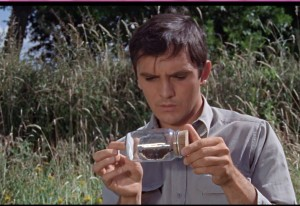 Freddie Clegg (Terence Stamp) is knelt down in a field holding a jar which contains a captured butterfly.