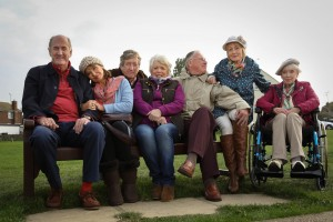 Boomers cast sitting on a bench - John (RUSS ABBOT), Maureen (STEPHANIE BEACHAM), Alan (PHILIP JACKSON), Joyce (ALISON STEADMAN), Trevor (JAMES SMITH), Carol (PAULA WILCOX), Joan (JUNE WHITFIELD)