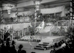 Black and white image of a beauty pageant - girls on the stage with an audience watching