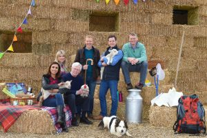 The Countyfile presenters on bails of hay L-R - Anita Rani, Ellie Harrison, John Craven, Adam Henson, Matt Baker, Peg, Tom Heap