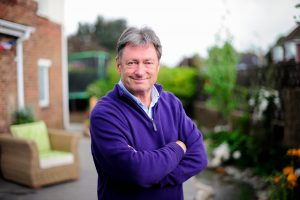 Alan Titchmarsh standing in a garden