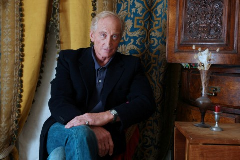 Charles Dance sat on a chair facing the camera. Colourful curtains are behind him.