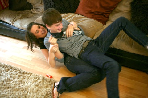 Emily and Tom Hughes fighting on the floor over the remote