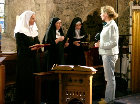 Susannah Harker, Brenda Blethyn, Rita Tushingham and Jan Dunn on the set of The Calling in a church holding bibles open in front of an alter