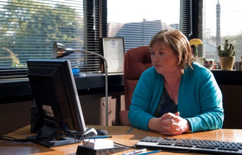 Pauline Quirke sat at a computer desk staring at her computer. windows with blinds can be seen behind her.