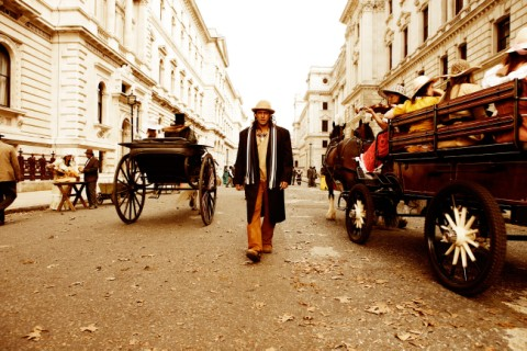 Salman Khan as Veer walking down a street with horse and carriages, white buildings are either side