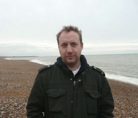 Photo of Derek Boyes standing on a pebbly beach