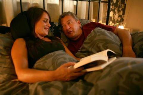 In bed, Jane holds a book with Simon looking at Jane