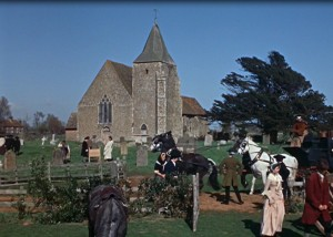Still taken from the film. Shot of st Clements Church from a distance with horses and villagers infront.