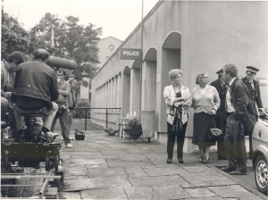 Civic Centre, Folkestone- concrete building with cast members being filmed by a crew in front of the building