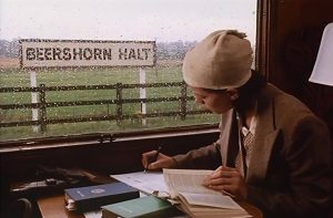 Kent and East Sussex Railway interior screenshot - a woman writing on a train