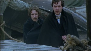 Eugene Wrayburn (Paul McGann) and Mortimer Lightwood (Dominic Mafham) wearing blankets amongst a collection of old wooden boats on teh dockyard