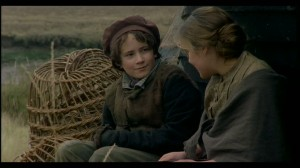 Young Pip (Gabriel Thompson) and Young Biddy (Laura Aikman) sat on the grass talking to each other, wicker baskets are behind them