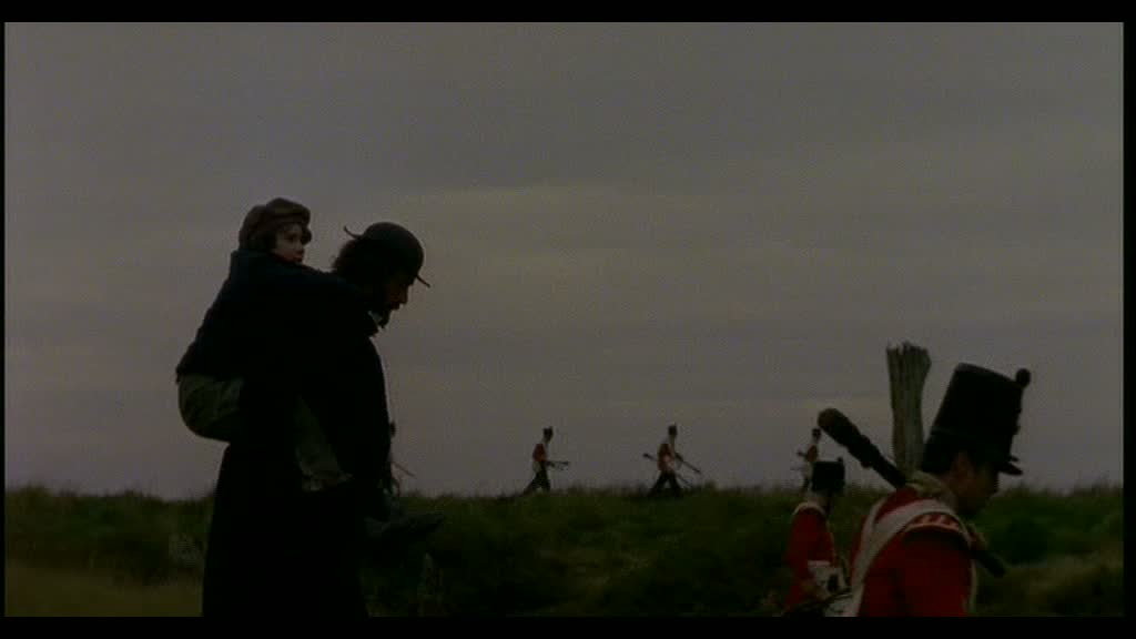 Joe Gargery (Clive Russell ) with Young Pip (Gabriel Thomson) in his shoulders walking through a field, soldiers are walking either side of them