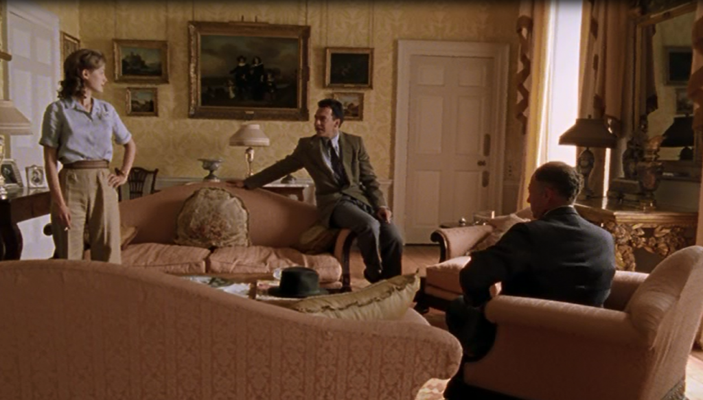 Joanna Kanska (standing), Dominic Mafham (sitting) are positioned by a sofa being interviewd by Foyle (Micheal Kitchen) who is opposite them. They are all in the Sitting room which has yellow patterned wallpaper and gold frames on the wall as decor.