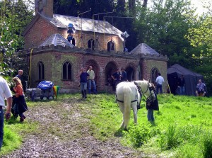 Behind the scenes filming of Bleak House at Cobham Hall - brick house with crew outside and a white horse on the grass in front