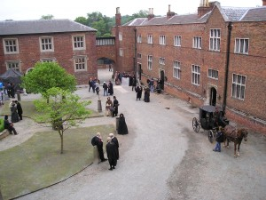 Behind the scenes filming of Bleak House at Cobham Hall - courtyard with people walking, horse and carriage driving past