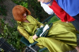 Emilia Fox in a green dress sitting on a chair and signing autographs