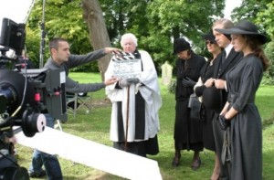Behind the scenes image of a crew member holding a clapper board, camera and a vicar, Kelly Brook and Harry Enfield at the graveyard