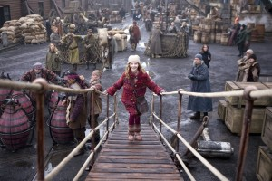 Dakota Blue Richards walking up a wooden ship plank towards the camera.