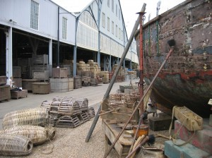 Behind the scenes image at The Historic Dockyard, Chatham- prop crates and barrels up against the building,