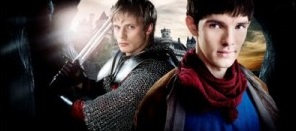 Bradley James and Colin Morgan staring at the camera, colin is holding a sword above his shoulders