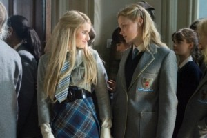 Emma Roberts and Kimberley Nixon in school uniform frowning at each other in a corridor full of students