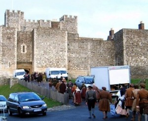 Behind the scenes at Dover Castle- queues of cast members entering the entrance to the castle along a concrete driveway. Cars and lorries are scattered along the side.