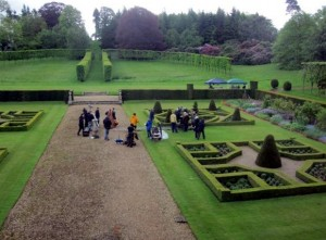 Behind the Scenes at Squerryes- formal gardens with grass and hedges- a film crew are in the centre on the grass and pathway
