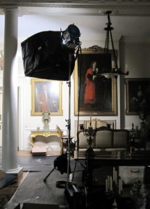 film light equipment pointed at a white wall with paintings on. Gold furniture is on the floor underneath.