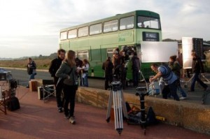 Filming on Princes Parade in Hythe - green double decker bus on the road with crew and filming equipment on the pavement