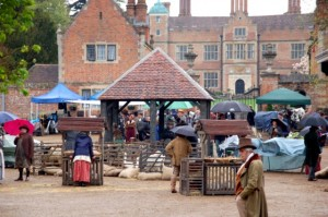 Market in front of Chilham Castle with actors walking around the stalls.