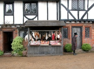 Wooden Meat Market Stall in front of a brick house with beams.