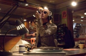 Rhys Ifans as Gavin in a recording studio speaking into a microphone with earphones on.