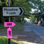 Street sign on the side of a road for Meadow Room, temporary pink sign reading LOC UNIT attached underneath.