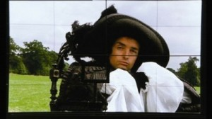 Anthony Higgins in costume staring at the camera in front of a field
